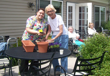 Nurse and resident planting flowers | Memory Care